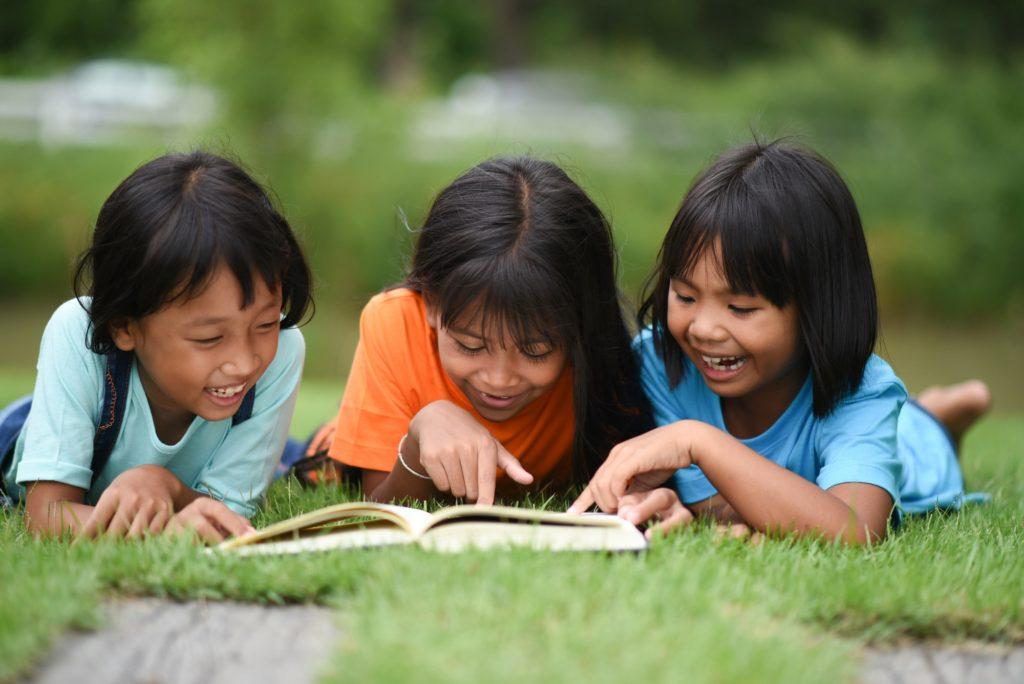 أفضل طرق تعلم القراءة والكتابةof children lying reading on grass field