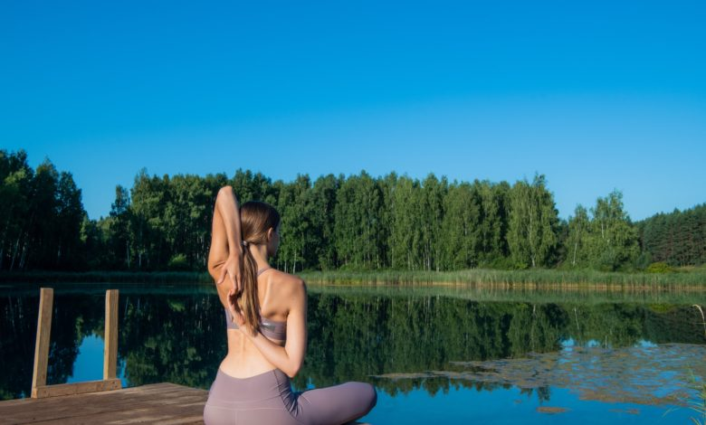 Young female practicing yoga against the sky on a sunrise. Pretty slim woman performs an exercise