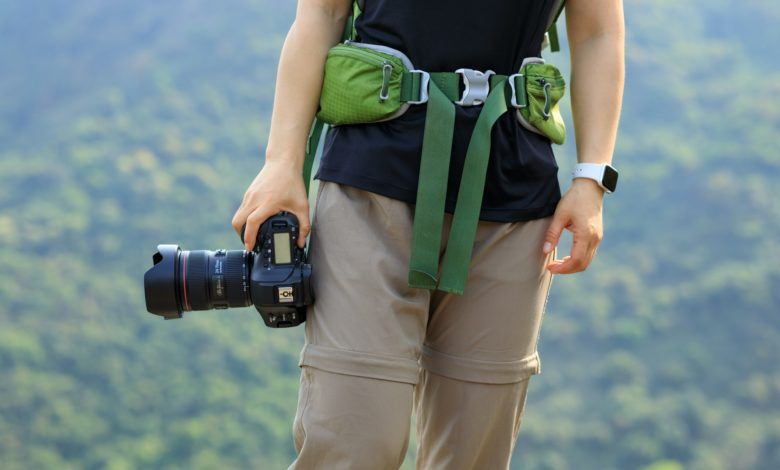 Woman photographer with camera in spring mountain