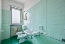 Old bathroom interior with green tiles
